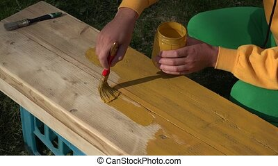 Worker painter hands painting wood surface with paintbrush in yellow color. Closeup. 4K