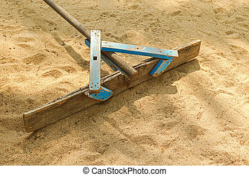 Handmade wooden stick to flatten, level and smooth surface of sand
