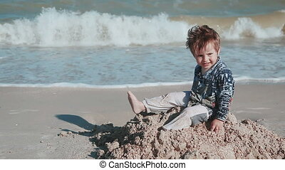 Boy age 2 years old, beautiful appearance, playing in the sand on the seashore. The wet clothes and fun. Summer day by the seaside.