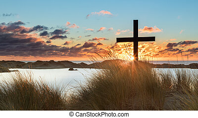 Lake Beach Sunset Cross - Black cross on a sand dune with a...