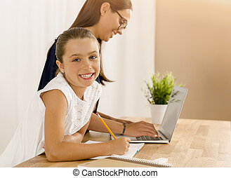 Making my homework - Mother and daugther at home doing...