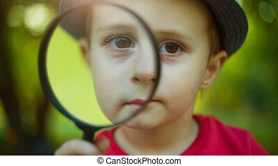 Boy looking through a magnifier - Boy looking through a...