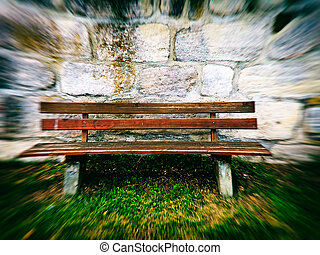 old abbey wall with park bench in retro view