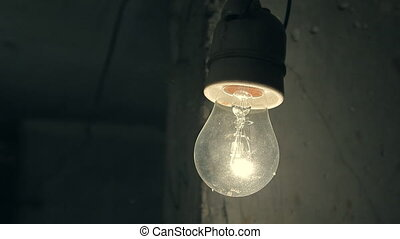 An old lamp is hanging in a dark room