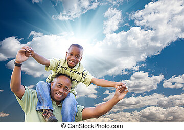 Happy African American Man with Child Over Clouds and Sky -...