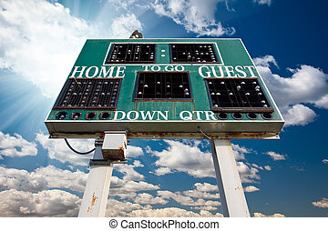 HIgh School Scoreboard Over Blue Sky with Clouds and Sun...