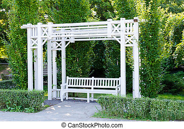 A beautiful gazebo and a bench painted in white in a park