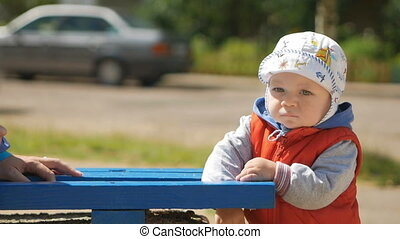 A boy stands near the bench on the playground with the...