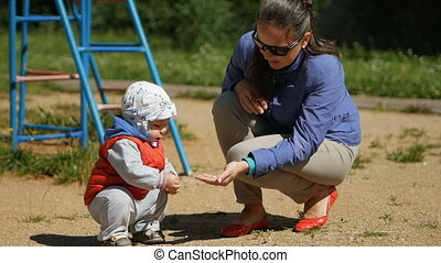 One year old kid playing with sand on the playground. Near the mother helps him with the game. Boy in the red waistcoat and a white headdress