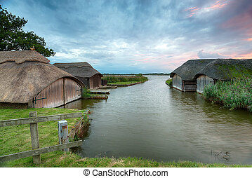 Boat Houses on the Norfolk Broads - Thatched boat sheds at...