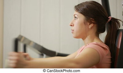 Beautiful girl trains in the gym woman engaged in a sports...