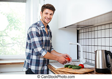 Cheerful young man washing vegetables on the kitchen -...