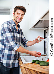 Happy young man standing and washing vegetables on the...