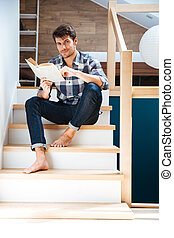 Young handsome man reading book while sitting on the stairs