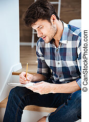 Concentrated young man sitting and writing in notepad at...