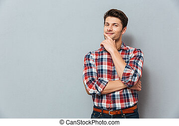 Handsome young pensive man standing and looking up -...