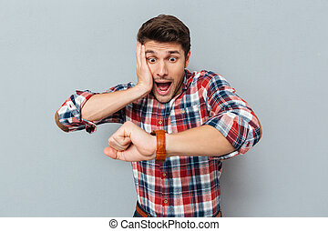 Astonished young man in checkered shirt looking at wristwatch