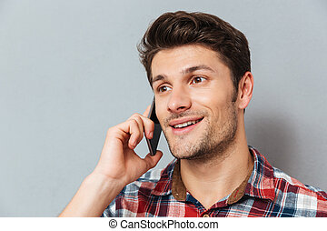 Closeup of happy young man talking on cell phone over grey...