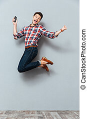 Happy man listening to music from cell phone and jumping -...