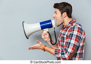 Side view portrait of a casual man yelling into megaphone...