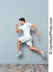 Young serious athletic man jumping isolated on the gray...