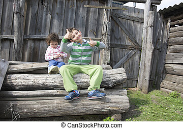 In the summer in the village on the street sitting on logs...