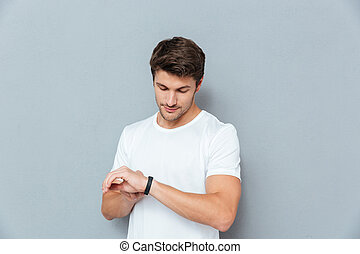 Serious young man standing and checking fitness tracker