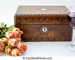 Background with pink dried roses, antique walnut jewelry box with mother of pearl inlay and red wine in crystal glass isolated on white background