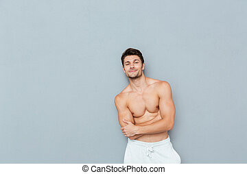Smiling confident shirtless young man standing with arms...