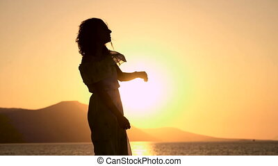 Young beautiful woman is dancing at the sunset next to the sea.