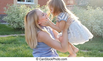 Happy mother hugging her daughter - Mother Giving Daughter...