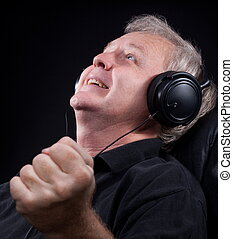 Intense emotion - Happy senior listening something in his...