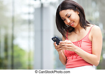 Woman texting - A shot of a mixed race woman texting on her...