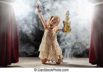 girl playing guitar on stage - Cute little child girl...