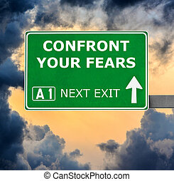 CONFRONT YOUR FEARS road sign against clear blue sky