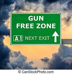 GUN FREE ZONE road sign against clear blue sky