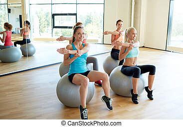 group of smiling women with exercise balls in gym - fitness,...