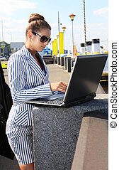 woman with computer on quay