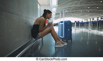 Passenger, woman siting in the airport, waiting for her flight using her phone