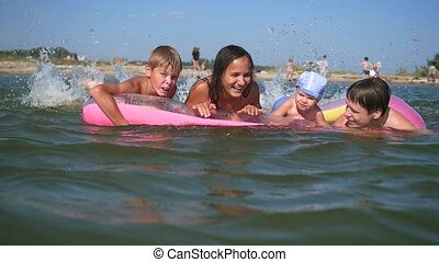 family having fun playing on inflatable mattress - family...