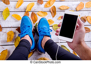 Runner in sports shoes holding smart phone. Autumn leaves. -...
