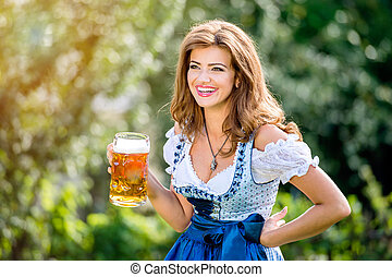 Woman in traditional bavarian dress holding mug of beer -...