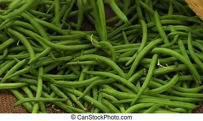 Fresh green beans over burlap cloth background at market...