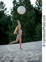 Girl with a ball on the beach - girl starts having fun on...