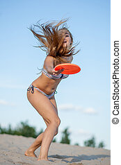 girl with frisbee - girl starts having fun on the beach on a...