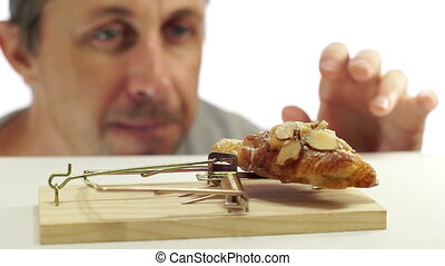 Man Looking at Bread In Mouse Trap - Close up shot of a man...