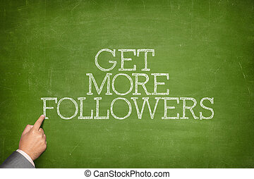 Get More Followers text on blackboard with businessman hand...
