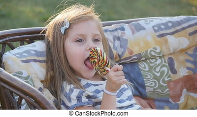 little girl with a lollipop - Happy little girl eating a...