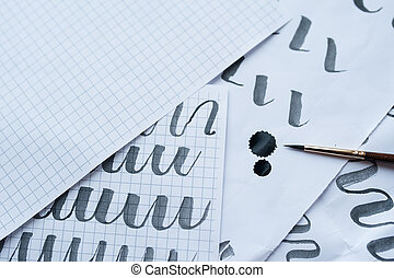 Antique calligraphy pens and ink blots with fancy writing on paper