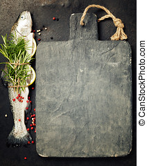 Raw rainbow trout with lemon, herbs and spice on rustic...
